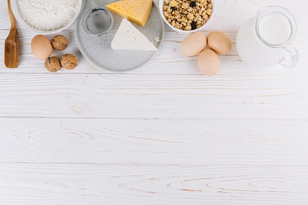 Bowl of cereals; milk; eggs; cheese; flour and walnuts on white wooden table Premium Photo
