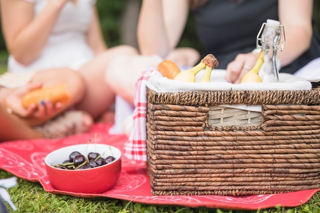 Bowl of cherry and picnic basket with people in the background Free Photo