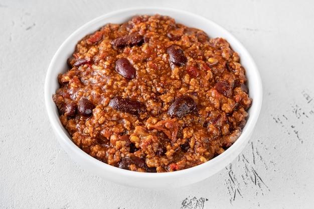 Bowl of chili con carne on white table Premium Photo