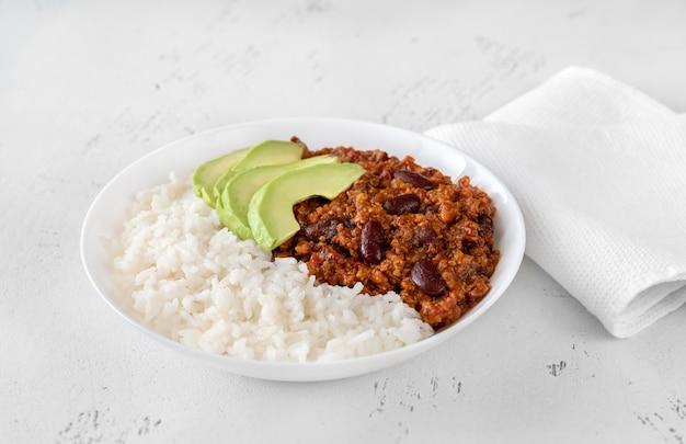 Bowl of chili con carne with rice, avocado and sour cream Premium Photo