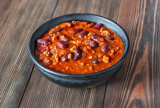 Bowl of chili con carne on a wooden table Premium Photo