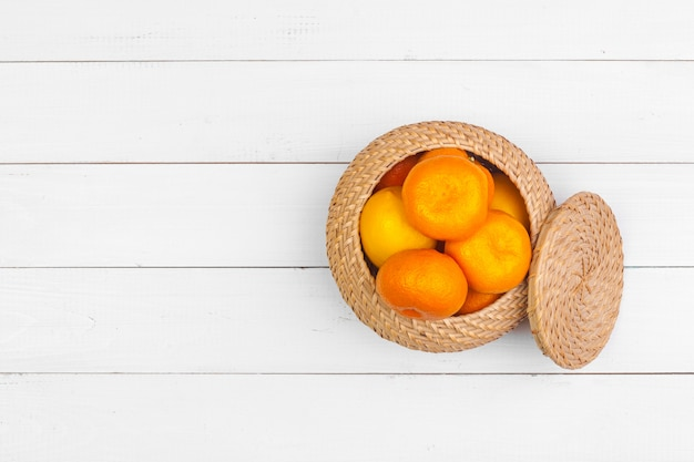Bowl of citrus fruits on white wooden surface , top view Premium Photo