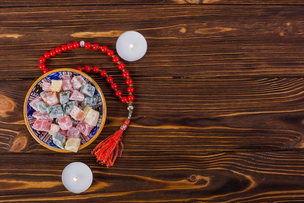 Bowl of colorful lukum and red holy rosary beads with lighted candles on wooden surface Free Photo