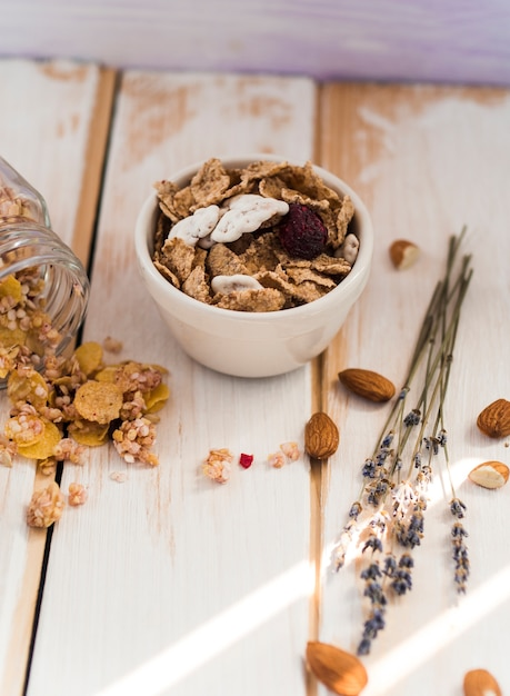 Bowl of cornflakes near spilled jar of granola and dry fruits on wooden surface Free Photo