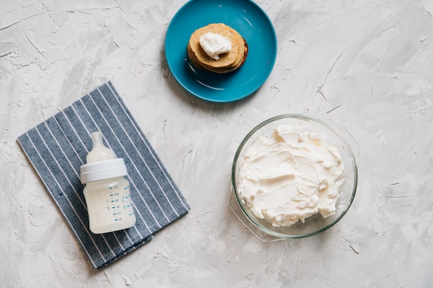 Bowl of cream cheese homemade in glass plate with pancakes and cottage cheese top view healthy food Premium Photo