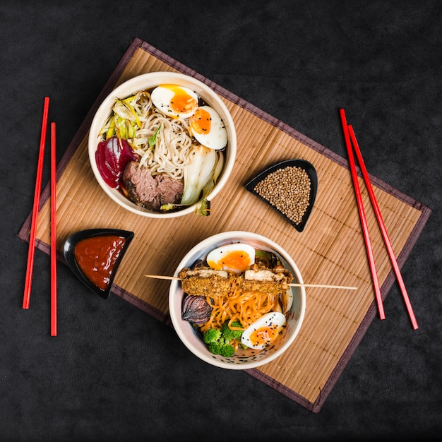 Bowl of different noodles with salad; eggs; sauce and coriander seeds with chopsticks on placemat against black background Free Photo
