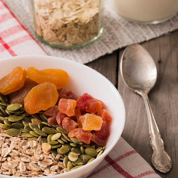 Bowl of dry fruits, pumpkin seeds and oat flakes on breakfast table Free Photo