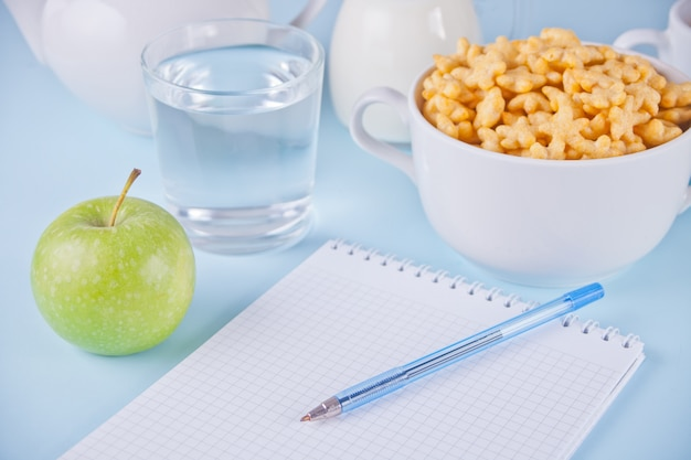 A bowl of dry star shaped cereal, cup of water, green apple Premium Photo