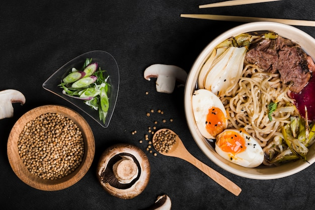 Bowl of eggs; noodles pork with coriander seeds; mushroom; chives and mushroom on black background Free Photo