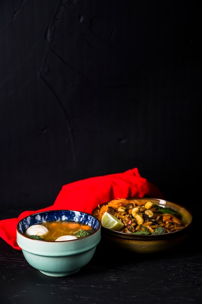 Bowl of fish ball and vegetable soup with noodles and red napkin against black background Free Photo