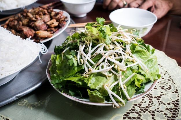 Bowl of fresh herbs and bean sprouts on a table Free Photo