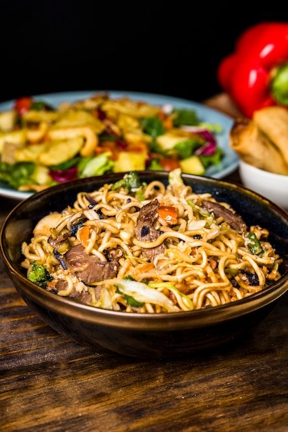 Bowl of fried stir noodles with beefs on wooden desk Free Photo