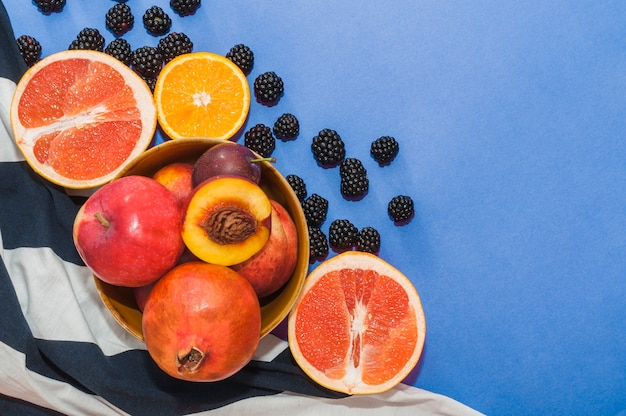 Bowl of fruits; citrus fruit and black berries on blue background Free Photo