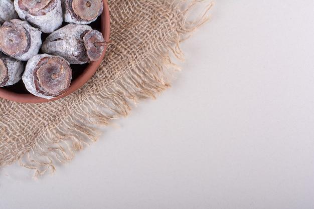 白い背景に干し柿と黄麻布でいっぱいのボウル。高品質の写真 無料写真