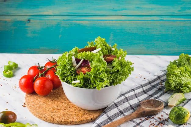 Bowl of green salad ingredient on wooden coaster Free Photo