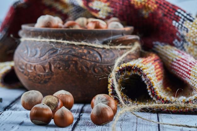 Una ciotola di nocciole sulla tavola di legno blu con tappeto intagliato Foto Gratuite
