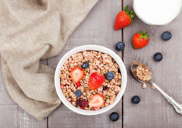 Bowl of healthy cereal granola with strawberries and blueberries and glass of milk on wooden board Premium Photo