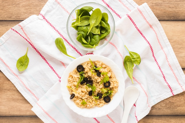 Bowl of healthy oats garnished with basil leaf and olive in bowl over cloth Free Photo