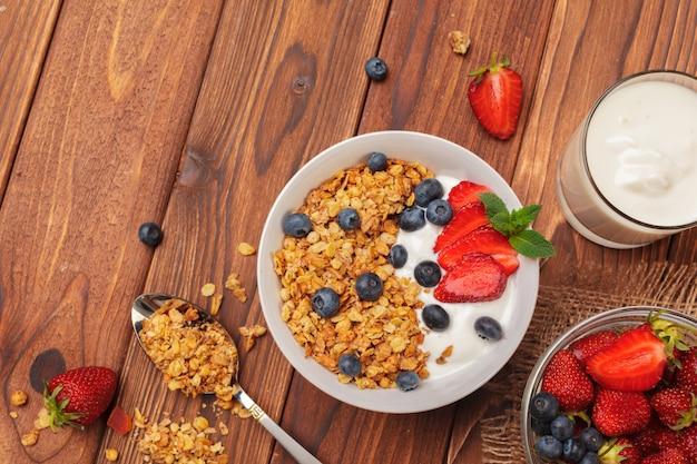Bowl of homemade granola with yogurt and fresh berries on wooden background Premium Photo