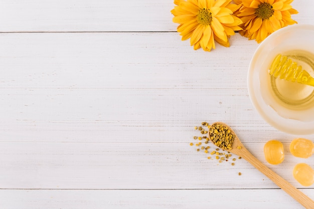Bowl of honey; candies; bee pollen seeds and flowers on wooden background Free Photo