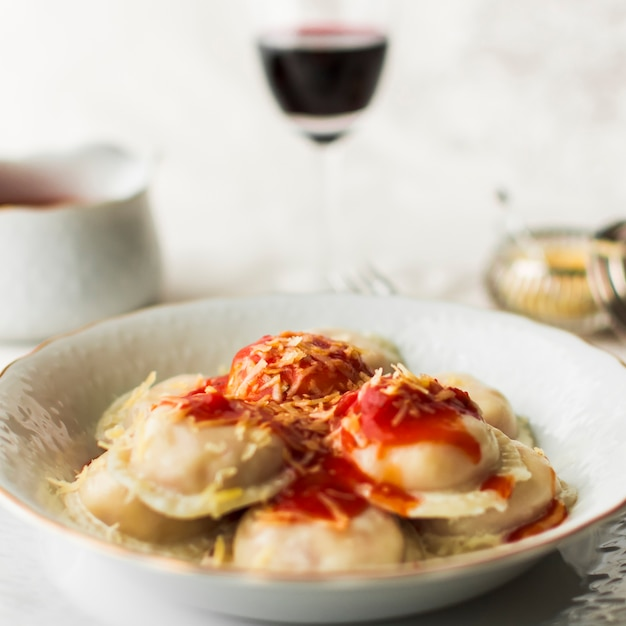 Bowl of italian ravioli pasta with spicy tomato sauce and cheese Free Photo