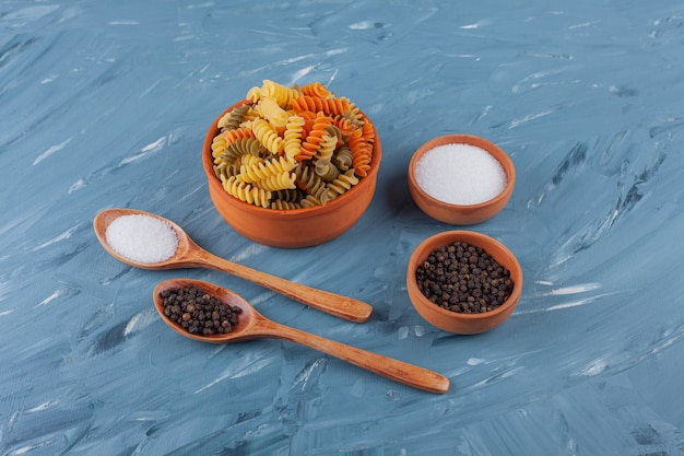 Una ciotola di pasta a spirale cruda multicolore con grani di sale e pepe. Foto Gratuite