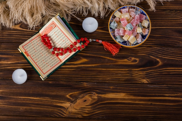 Bowl of multicolored lukum and red holy rosary beads and kuran with candles on wooden surface Free Photo