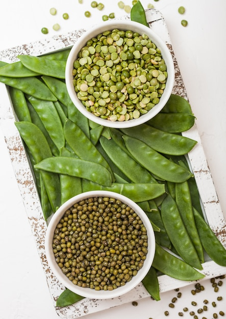 Bowl of  mung beans and split peaswith raw organic mangetout in vintage wooden box on white kitchen backround Premium Photo