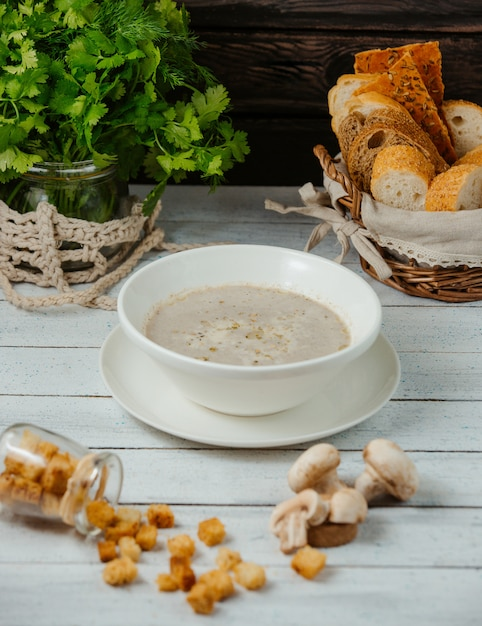 A bowl of mushroom soup served with bread stuffing, corriander on jar Free Photo