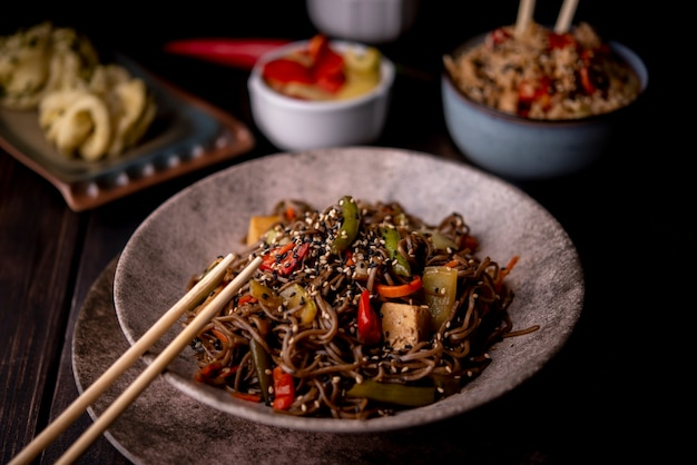 Bowl of noodles with assortment of asian food Free Photo