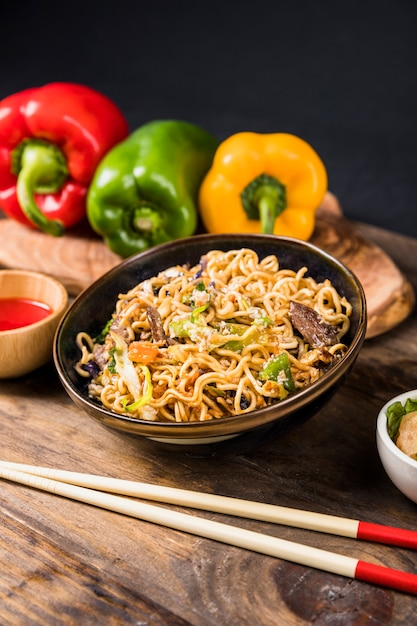 Bowl of noodles with bell peppers and chopstick on wooden desk Free Photo