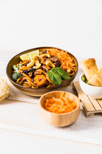 Bowl of noodles with spring roll and grated carrot on wooden table against white backdrop Free Photo
