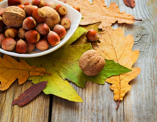 Bowl of nuts and autumn leaves on the old wooden table Premium Photo