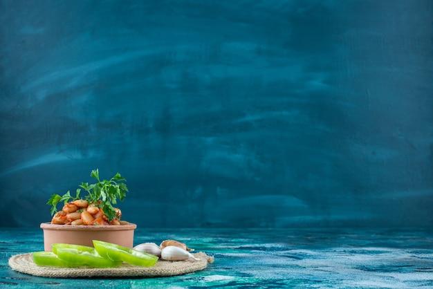 파란색에 삼발이에 구운 콩, 마늘, 후추의 그릇. 무료 사진