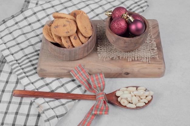 白いテーブルの上のチップクッキーとクリスマスボールのボウル。高品質の写真 無料写真
