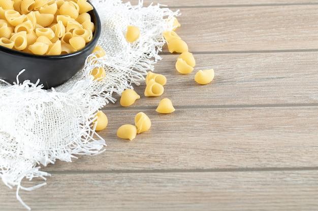 黄麻布と木製のテーブルの上の乾燥パスタのボウル。 無料写真