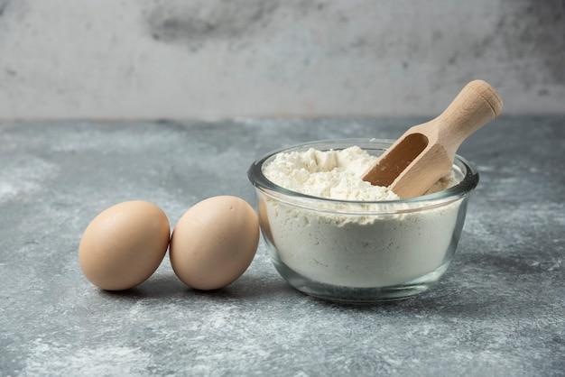 大理石のテーブルに小麦粉と卵のボウル。 無料写真