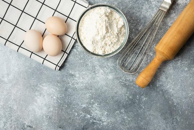 Чаша с мукой, яйцами и кухонными принадлежностями на мраморной поверхности. Бесплатные Фотографии