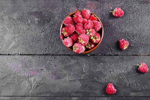 暗い木製のテーブルに新鮮な赤いラズベリーのボウル。 無料写真