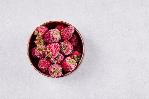 白い背景の上の新鮮な赤いラズベリーのボウル。 無料写真
