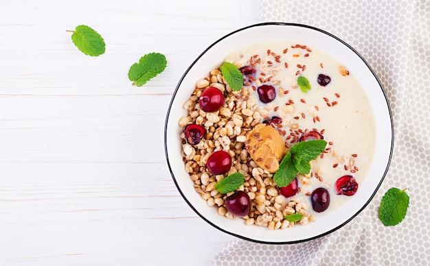Чаша из домашней гранолы с банановым пюре, арахисовым маслом и свежими ягодами Бесплатные Фотографии