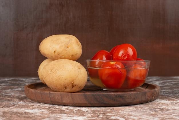 Чаша маринованных помидоров и отварного картофеля на деревянной тарелке. Бесплатные Фотографии