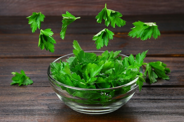 A bowl of parsley with flying leaves on a wooden table. levitation. Premium Photo
