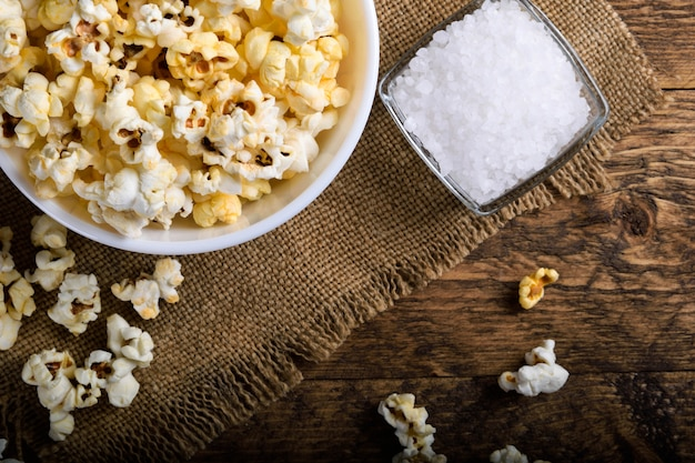 A bowl of popcorn on a wooden table. Premium Photo