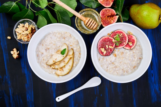 A bowl of porridge with pears slices and walnuts and porridge with figs Premium Photo