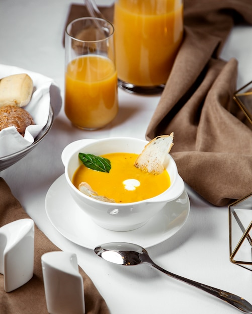 A bowl of pumpkin soup garnished with toast and cream Free Photo