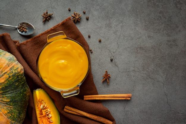 Ciotola di zuppa di zucca posto su tessuto marrone Foto Gratuite