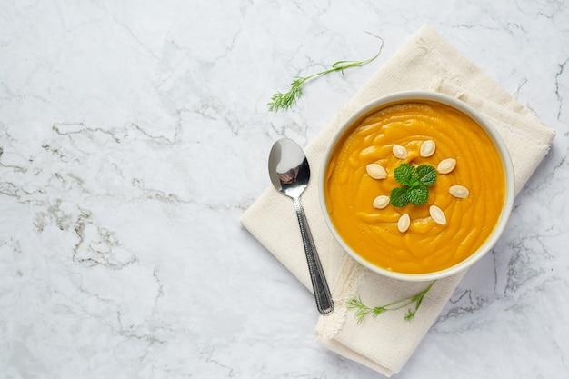 Ciotola di zuppa di zucca posto su tessuto bianco Foto Gratuite