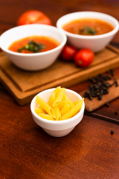Bowl of raw penne pasta with tomato sauce and black peppercorn on wooden table Free Photo