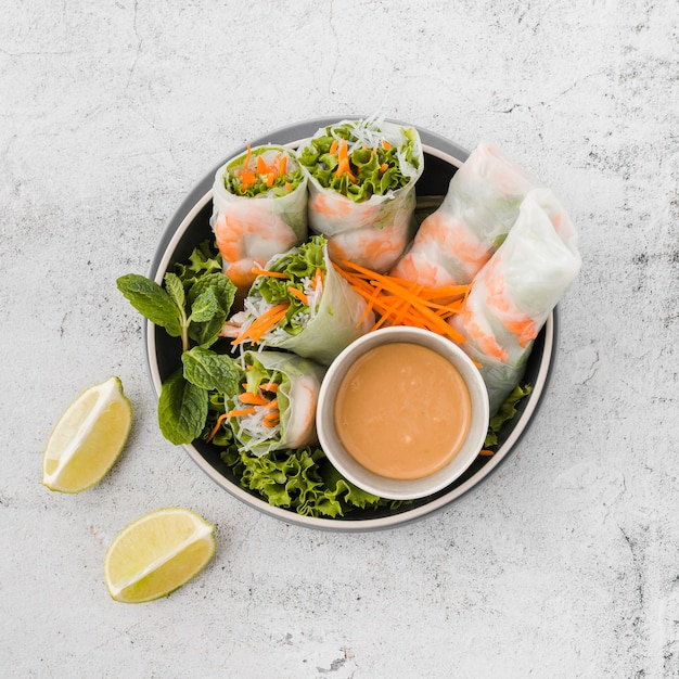 Bowl of shrimp rolls with sauce and lemon slices Free Photo